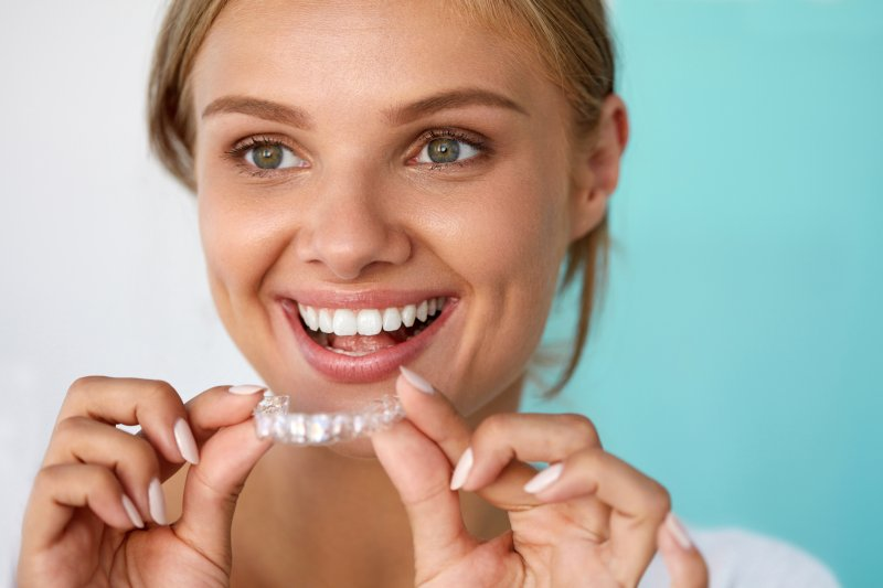 A woman smiling and holding at-home aligners.