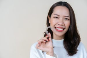 Woman holding Invisalign in Bartlesville while smiling